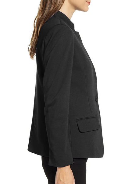 Side view of model wearing black single button inverted lapel flap pockets blazer