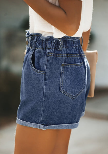 Side view of model wearing dark blue elastic-waist button front roll-over denim shorts