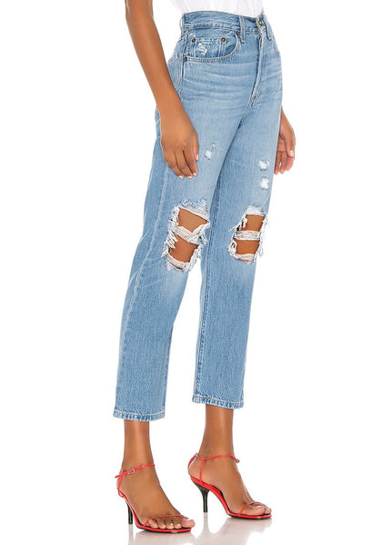 Side view of model wearing light blue high-waist ripped denim cropped jeans