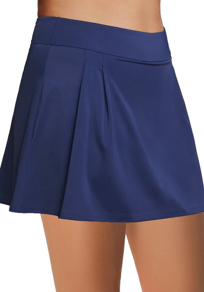 Side view of model wearing navy blue pleated side mid-waist swim skirt