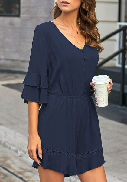 Side view of model wearing navy ruffle 34 sleeves elastic-waist button loop romper