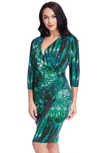 Slight left angled view of model in plus size green leaf-printed midi wrap dress