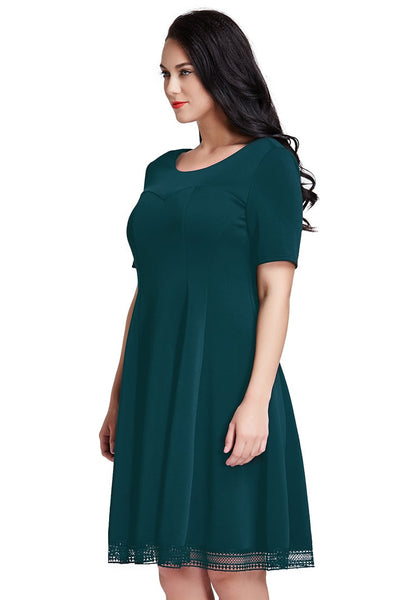 Slight left side view of lady in plus size deep green short-sleeves skater dress