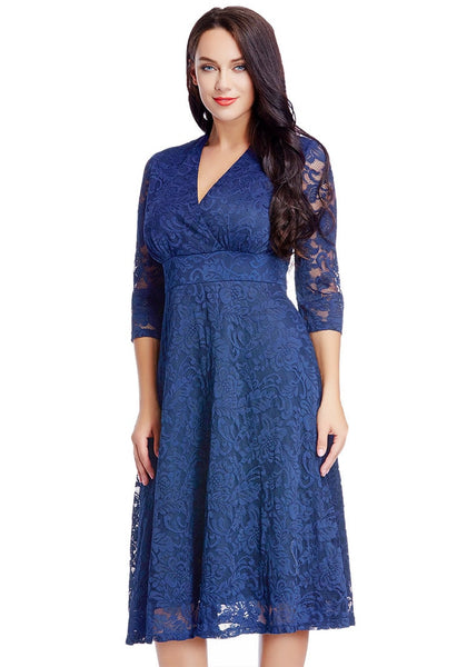 Slight right angle view of model in plus size royal blue lace surplice midi dress