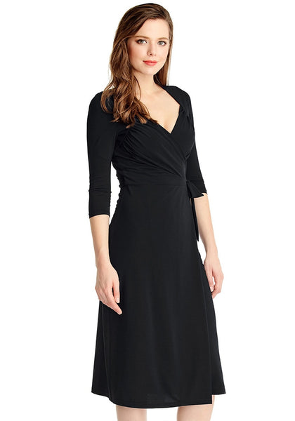 Slight right angled view of model in black sweetheart neckline wrap dress
