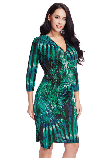 Slight right angled view of model in plus size green leaf-printed midi wrap dress