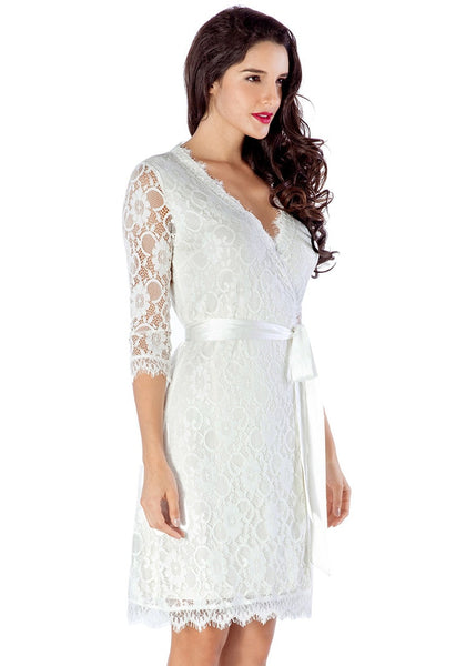 Slight right angled view of model in white lace overlay plunge wrap-style dress