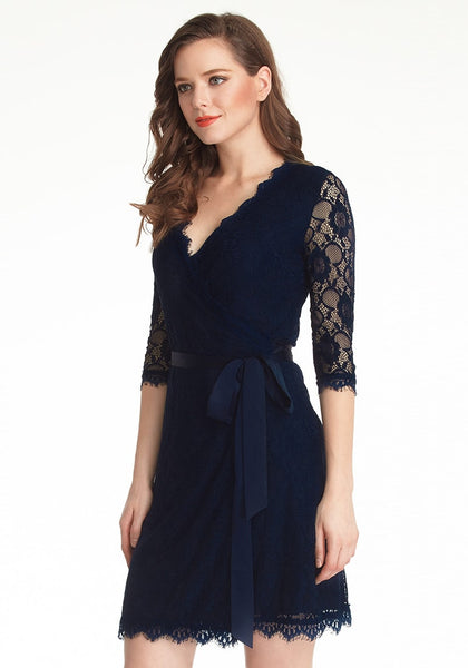 Slightly angled left side shot of model in navy blue lace overlay plunge wrap-style dress