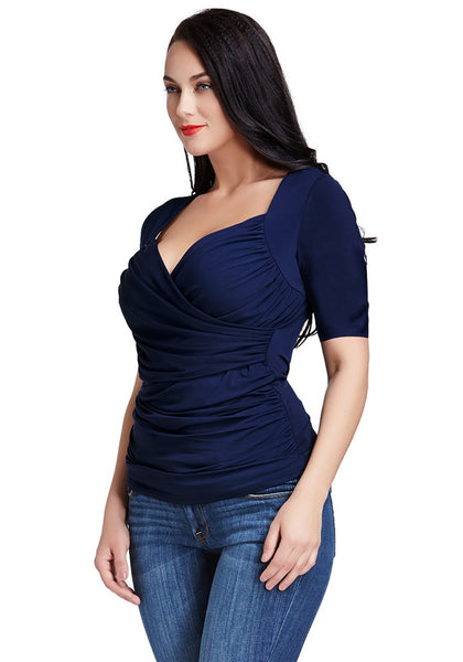 Slightly angled left side view of a black-haired model in a navy blue ruched surplice top