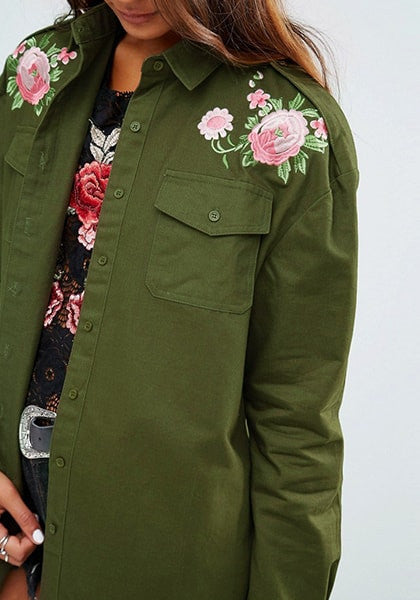 Slightly angled medium shot of  lady in  army green floral-embroidered shoulder shirt
