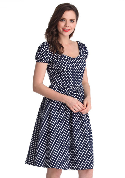 Slightly angled right side view of a brunette girl in a navy blue polka dot dress