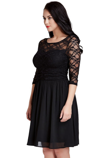 Slightly angled shot of dark-haired woman in black lace crop-sleeves skater dress