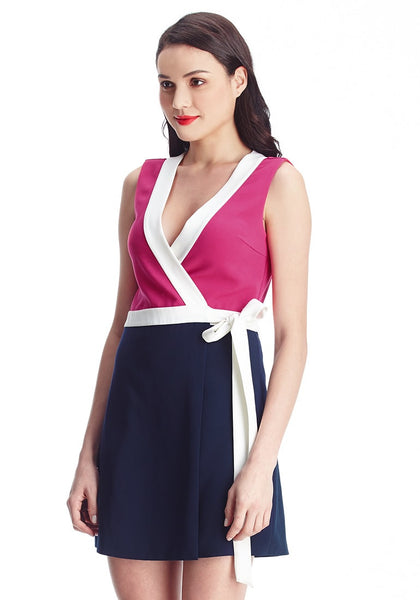 Slightly angled shot of lady in pink and navy sleeveless wrap-style dress