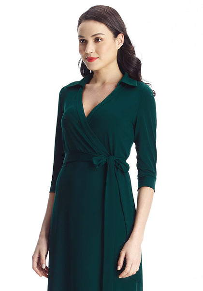 Slightly angled shot of model in dark green plunge wrap belted maxi dress