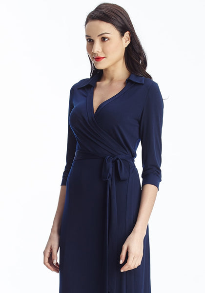 Slightly angled shot of model in navy blue plunge wrap belted maxi dress