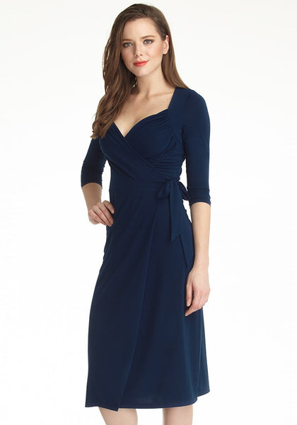 Slightly angled shot of model in navy blue sweetheart neckline wrap dress with one hand on hip