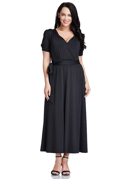 Slightly angled shot of model in plus size black surplice belted long dress