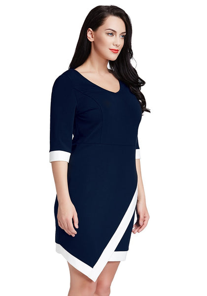Slightly angled shot of model in plus size navy asymmetric wrap bodycon dress