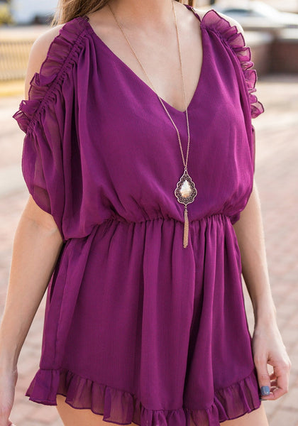 Slightly angled shot of model in purple cold-shoulder ruffled romper