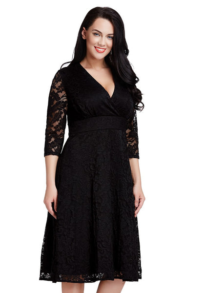 Slightly angled shot of woman in black lace surplice midi dress