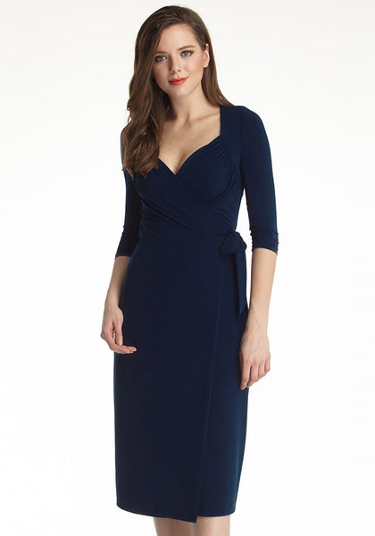 Slightly angled shot of woman in navy blue sweetheart neckline wrap dress