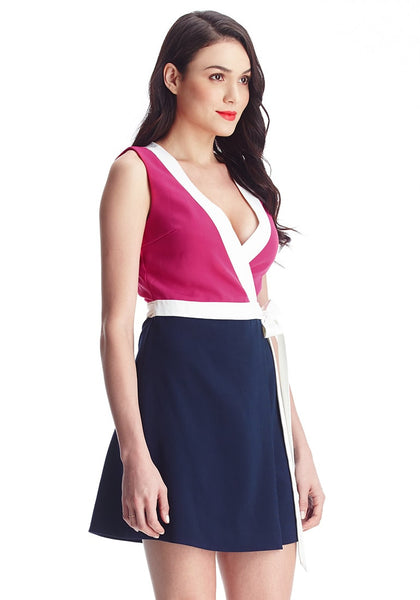 Slightly angled shot of woman in pink and navy sleeveless wrap-style dress