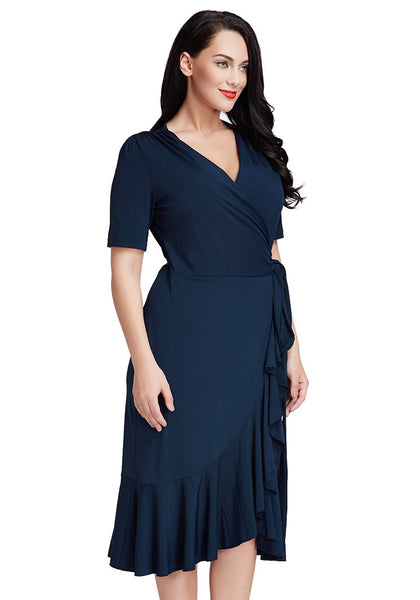Slightly angled shot of woman in plus size navy asymmetrical ruffled wrap dress