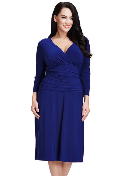 Slightly angled view of model in plus size royal blue ruched waist dress