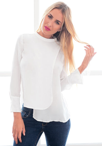 Slightly angled view of model in white asymmetric layered chiffon blouse with one hand touching hair