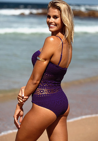 Slightly left angled shot of blonde woman in purple lace halter swimsuit