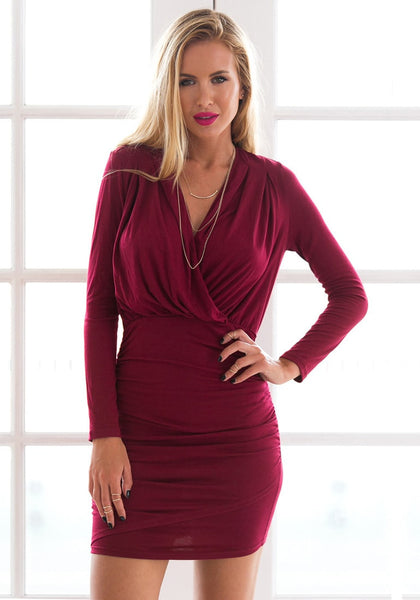 Sultry woman in falu red ruched wrap-style dress