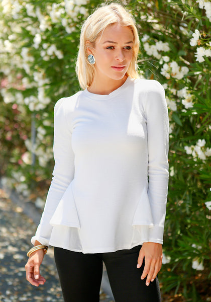 Front view of model in white peplum ruffled top