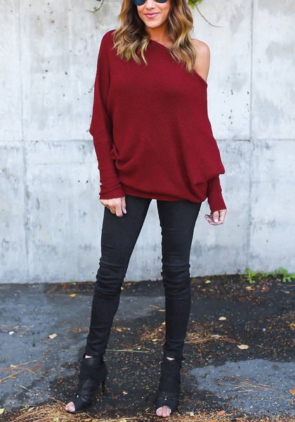 Whole body shot of model in burgundy off-shoulder bat sleeves sweater