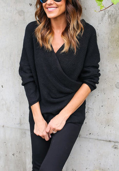 Woman leaning on a wall wearing black ribbed wrap sweater