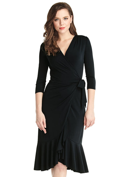 Woman poses in black asymmetrical ruffled wrap dress