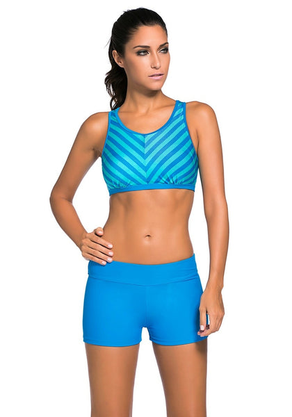 Woman poses in light blue striped sports bra two-piece set