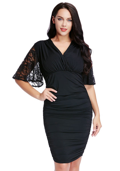 Woman poses in plus size black ruching bodycon dress with one hand on hip