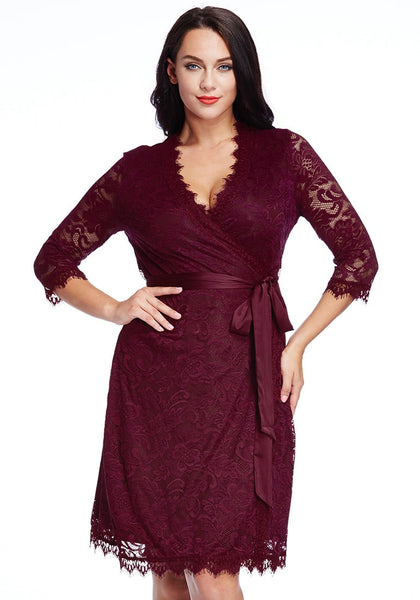 Woman poses in plus size burgundy lace crop sleeves wrap with one hand at waist