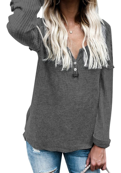Woman poses wearing grey front buttons roll-up sleeves textured top