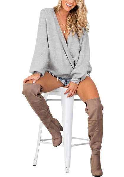 Woman poses wearing light grey lantern sleeves surplice sweater