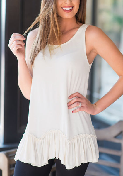 Woman poses wearing white ruffle-hem crew neck sleeveless tunic