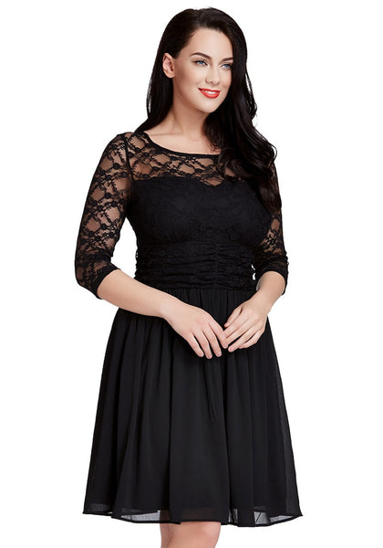 Woman wearing black lace crop-sleeves skater dress poses with hands in front