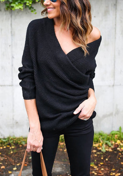 Woman wearing black ribbed wrap sweater in one-shoulder style