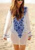 Woman wearing white floral embroidered v neck beach cover-up by the beach
