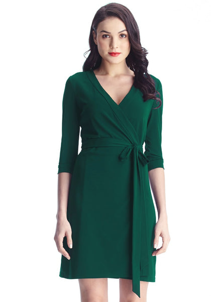 front view of model in Angled shot of model in green plunge wrap-style belted dress