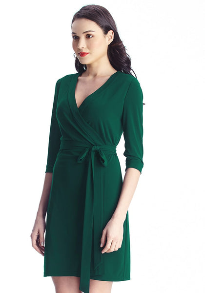 left sight view of model in Angled shot of model in green plunge wrap-style belted dress
