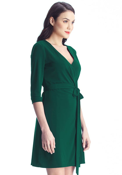 right sight view of model in Angled shot of model in green plunge wrap-style belted dress