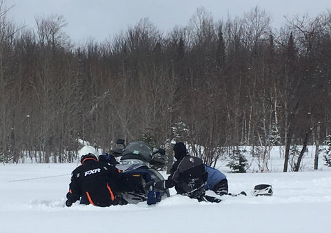 Digging out a snowmobile stuck in snow
