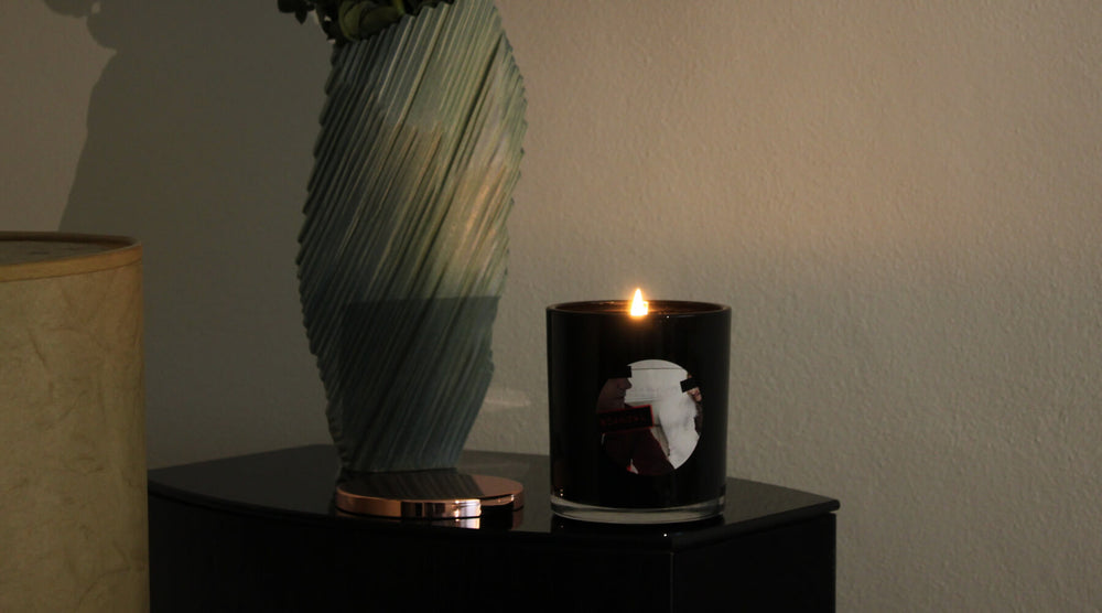 Luxury scented candle sitting next to vase and lamp. Scandal Candle from Candle Monster. Signature Series
