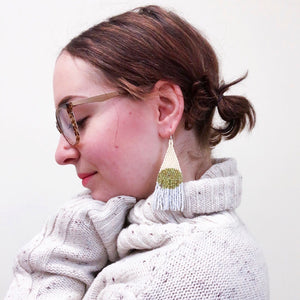 Bold beaded earrings in olive green on a woman with glasses
